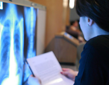 Students examining X-rays of a human chest and abdomen