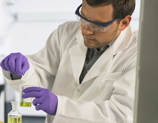 A student wearing a lab coat, goggles and gloves at a lab bench