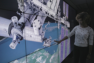 A woman standing in front of a screen with an image of a satellite over Ear