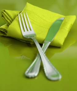 A place setting with green linens